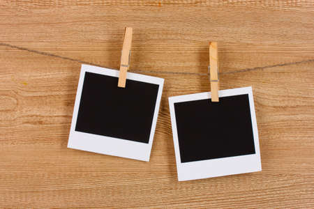 Photo papers hanging on the clothesline on wooden background photo