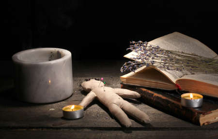 Voodoo doll boy on a wooden table in the candlelight photo