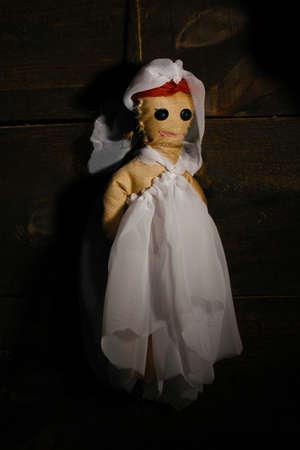 impiccata: Appeso voodoo bambola-sposa su sfondo di legno