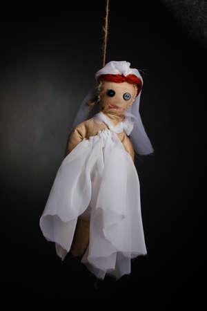 ahorcada: Colgado del vudú muñeca de niña-novia sobre fondo gris Foto de archivo