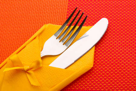 Fork and knife in a yellow cloth with a bow on a red tablecloth photo