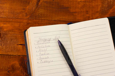 Shoping list and pen on wooden table photo