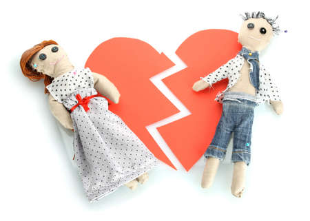 Two voodoo dolls boy and girl on the broken heart isolated on white photo