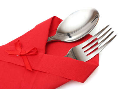 Fork and spoon in a red cloth with a bow isolated on white photo
