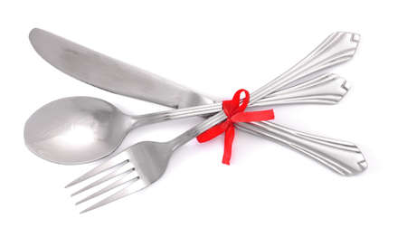 Silver fork and spoon, knife tied with a red ribbon isolated on white photo