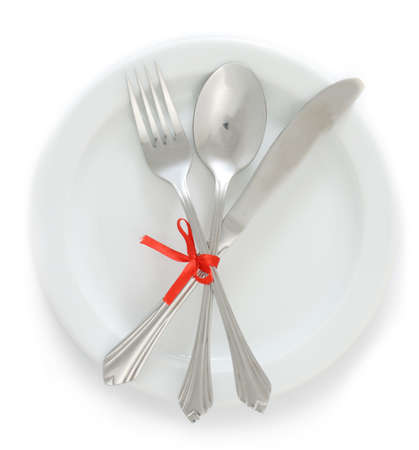 White empty plate with silver fork and spoon, knife tied with a red ribbon isolated on white photo