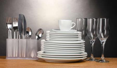 Saubere Teller, Gläser, Becher und Besteck auf Holztisch auf grauem Hintergrund Standard-Bild