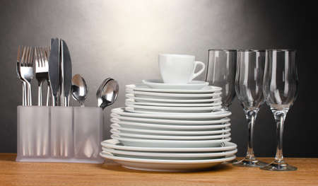 Schone borden, glazen, beker en bestek op houten tafel op een grijze achtergrond Stockfoto