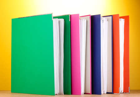 bright office folders on wooden table on yellow background  photo