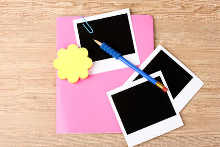 Photo papers and pink notebook on wooden background photo