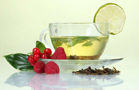 green tea in transparent cup with lime and berry on yellow background photo
