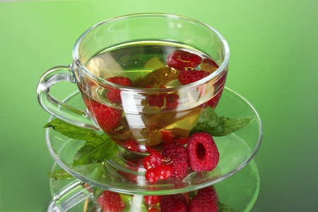 green tea in transparent cup with mint and berry photo