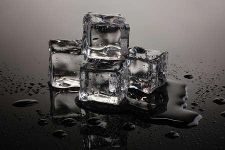 melting ice: Derritiendo cubitos de hielo sobre fondo gris