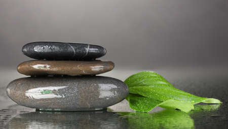 spa stones with water drops and leaves on black background photo