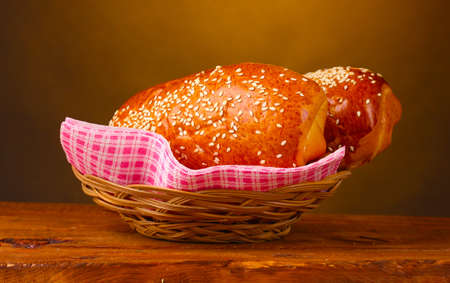Baked bread in basket on wooden table on brown background photo