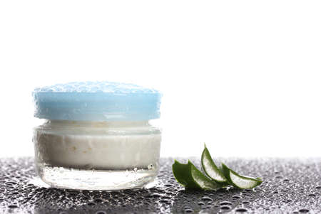 Closed glass jar of cream and aloe on black table with water droplets isolated on white photo