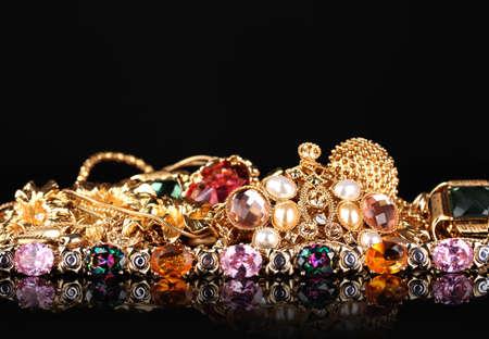 Diverse gouden sieraden op zwarte achtergrond Stockfoto