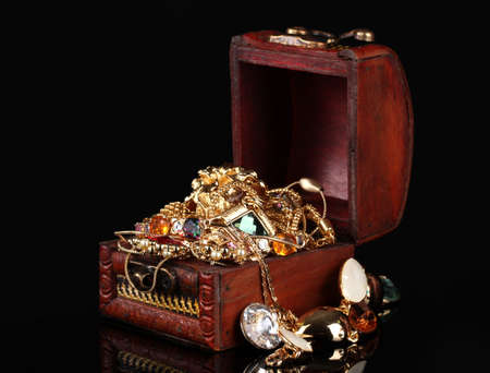 Wooden chest full of gold jewelry on black background Stock Photo - 11999945