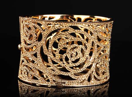 beautiful golden bracelet on black background Stock Photo - 11999439