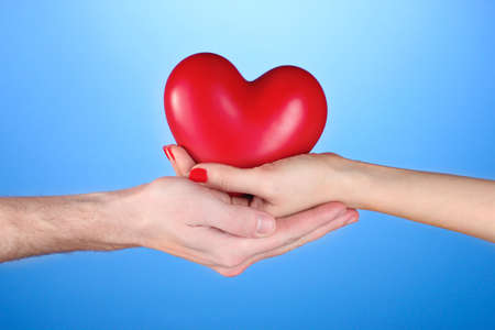Man and woman holding red heart in hands on blue background photo