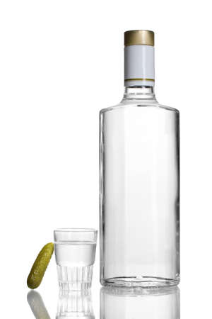 Bottle of vodka and wineglass with cucumber isolated on white photo