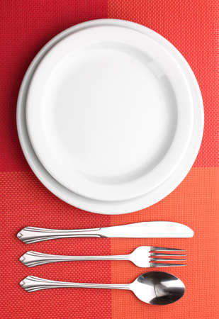 White empty plate with fork, spoon and knife on a red tablecloth photo