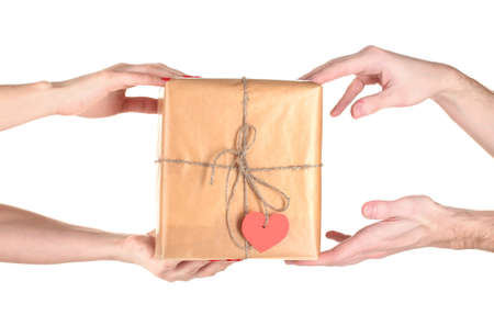 Womans hand giving parcel with blank heart-shaped label to man isolated on white photo