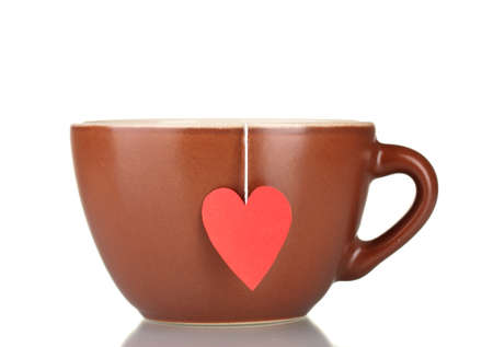 Brown cup and tea bag with red heart-shaped label isolated on white photo