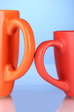 Two colored cups handles close-up on blue background photo