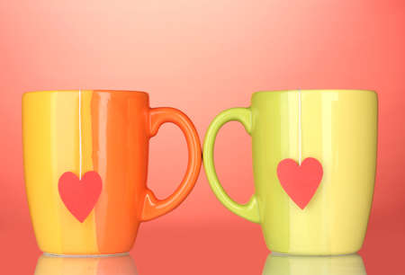 Two cups and tea bags with red heart-shaped label on red background photo