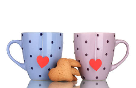 Two cups with tea bags and cookies isolated on white Stock Photo - 12098454