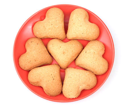 Heart-shaped cookies on red saucer isolated on white Stock Photo - 12099260