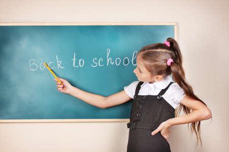 school children uniform: beautiful little girl standing near blackboard in the classroom Stock Photo