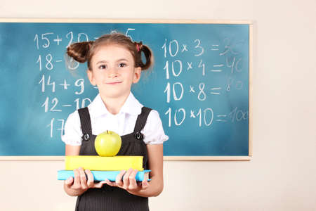 beautiful little girl with books and apple standing near blackboard in classroom photo