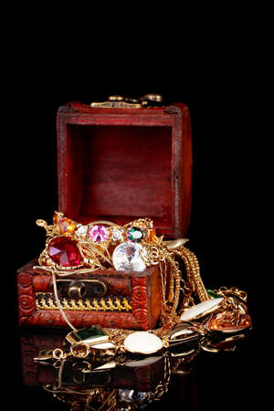 Wooden chest full of gold jewelry on black background Stock Photo - 12099673