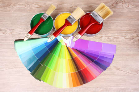 open tin cans with paint and palette on wooden background photo