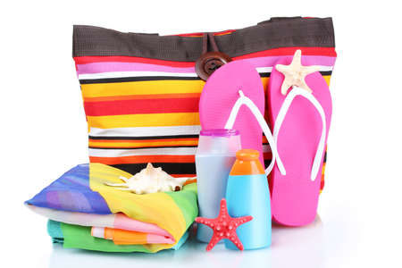 flip flops on the beach: bright striped beach bag and beach items isolated on white