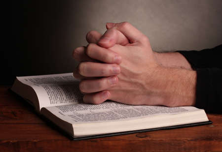 Hands folded in prayer over a Holy bible on wooden table on grey background photo