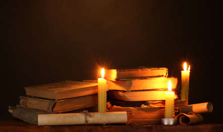 Pile of old books with candle and scroll in dark Stock Photo - 12101177