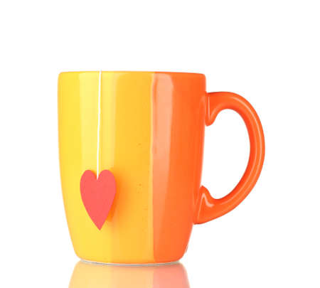 Orange cup and tea bag with red heart-shaped label isolated on white photo