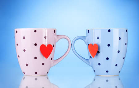 Two cups and tea bags with red heart-shaped label on blue background photo