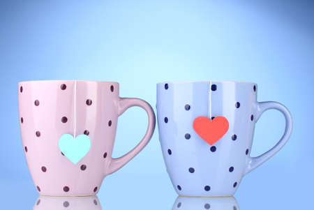 Two cups and tea bags with red and blue heart-shaped label on blue background photo