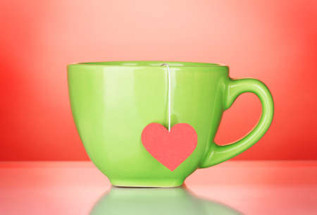 Green cup and tea bag with red heart-shaped label on red background photo