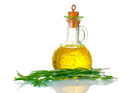 Oil in a bottle and fresh rosemary isolated on white photo