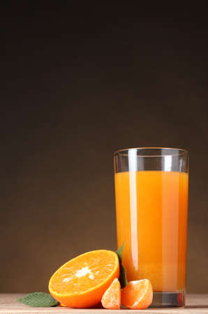 Tangerines and juice glass on wooden table on brown background photo