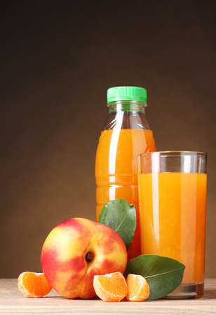 Nectarine and juice glass on wooden table on brown background photo