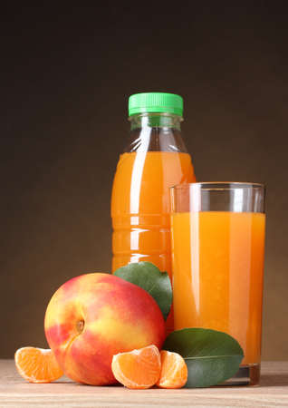 Nectarine, juice glass and bottle on wooden table on brown background photo