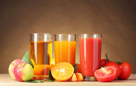Different juices and fruits on wooden table on brown background Stock Photo - 12108415