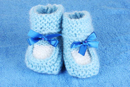 cuddly baby: Blue baby booties on blue background Stock Photo