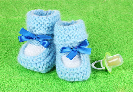 cuddly baby: Blue baby booties and pacifier on green background